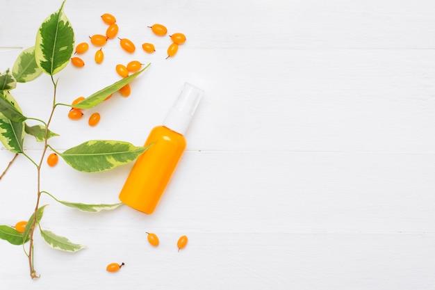 自然なスキンケア化粧品のボトル。白い背景の海クロウメモドキハンドクリーム。ハーブ化粧品。トップビュー、コピースペース。