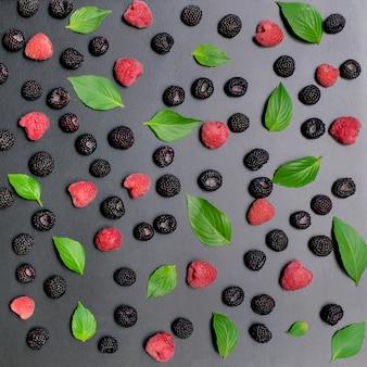 Черная и красная малина с зелеными листьями на темном фоне. квадрат для инстаграм.