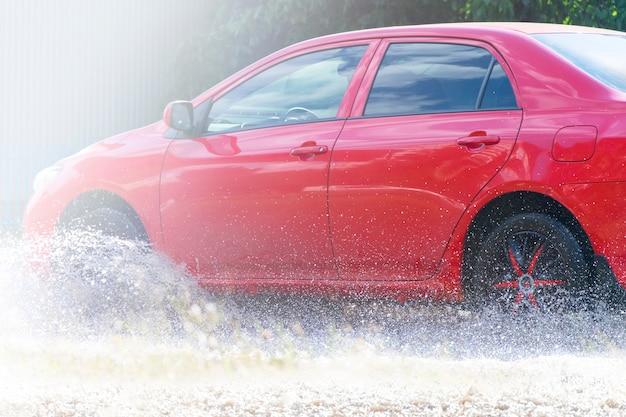 Красный автомобиль едет по большой луже. всплеск воды.