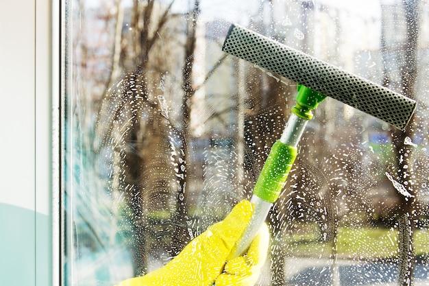 特別なスクレーパーで窓を掃除する