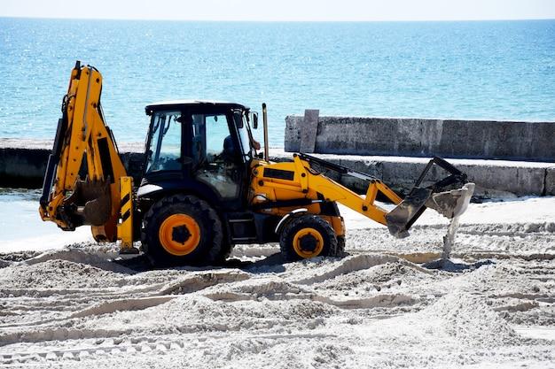 トラクターと砂。ビーチでの修理作業。
