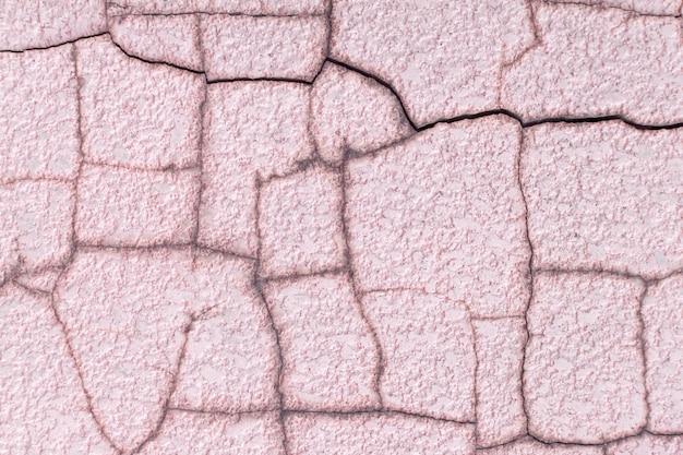 ピンクのひびの入った壁の背景のテクスチャ