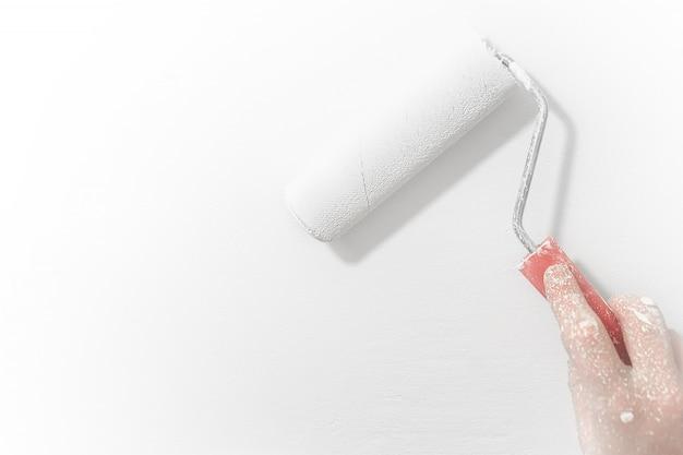 Мужской ручной росписью стены с валиком. покраска стен, ремонт, белого цвета