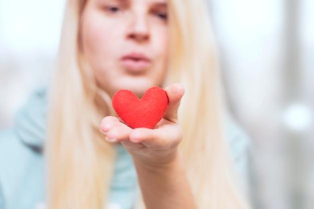 女の子はキスを送信します。手のひらのクローズアップの心。