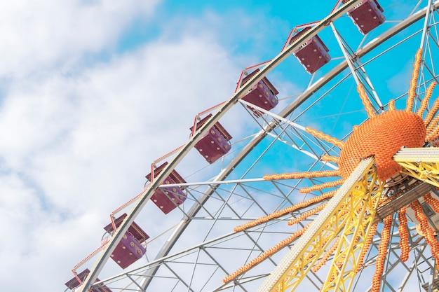 Аттракцион колесо обозрения на фоне голубого неба с облаками