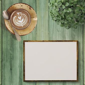 カプチーノコーヒーと緑色の木製の背景に空のフレーム