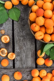 素朴な木製のテーブルに美味しい完熟アプリコット。大まかな木製の背景に生の果物。ベジタリアンフード。上からの眺め