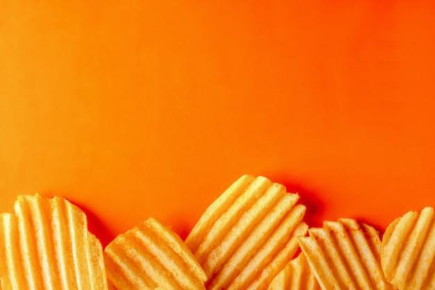 明るいオレンジ色の背景に波状のうねのあるポテトチップスをしわにします。スペース、レイアウト、コンセプトをコピーします。