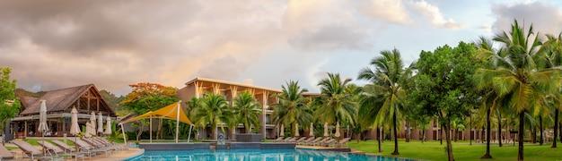 Панорама шикарного пятизвездочного отеля с бассейном, песками кататани. вечерний порядок, пальмы и зеленая трава. место отдыха