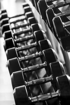 黒のダンベルセット。スポーツフィットネスセンター、ウェイトトレーニング機器コンセプトのラックに多くの金属ダンベルを閉じます。垂直レイアウト。