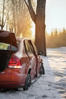 車と冬の道路上の氷。車は冬に事故に遭い、木にぶつかり、道路の脇の溝に滑り込みました。