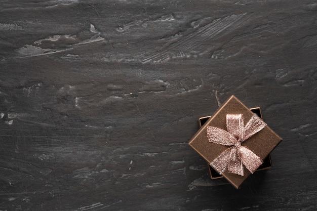 Подарок, подарочная коробка справа на темном и даже черном текстурном фоне.