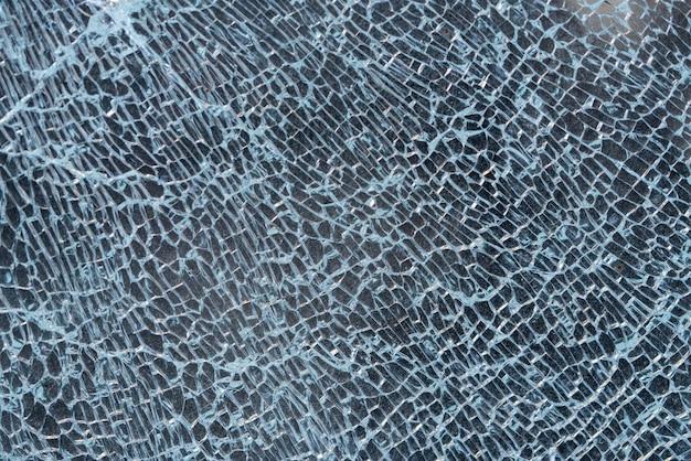 割れたガラスの背景。クモの巣で割れたガラス窓。