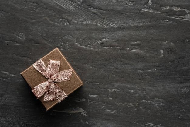 Подарок, подарочная коробка влево на темном и даже черном текстурном