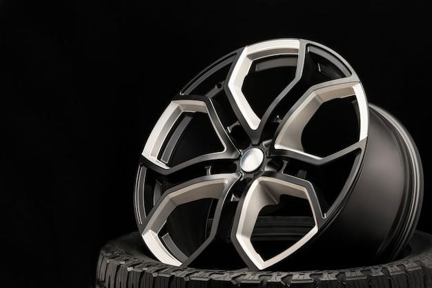 Колесо из алюминиевого сплава. премиум литой, дизайн спиц и обода колеса, белые и черные элементы на темном фоне крупным планом