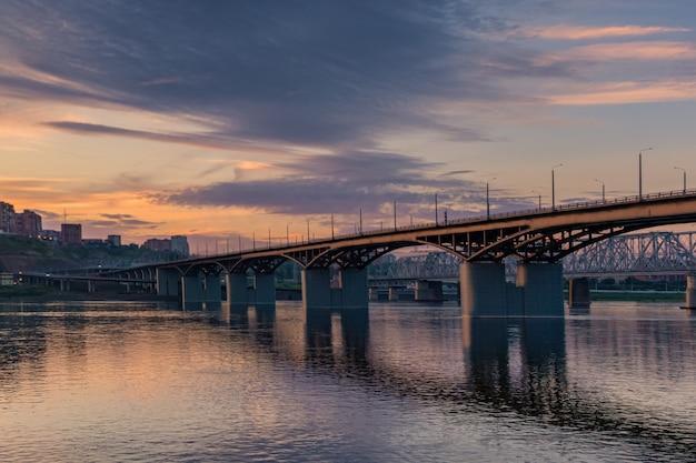 Мост через енисей, вечерний закат. красноярск, россия. панорама вечернего города