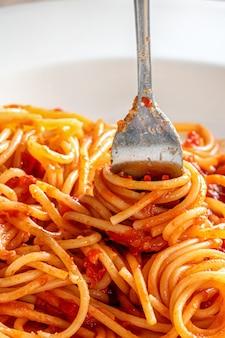 ケチャップソース、垂直方向の画像と白いプレートにイタリアのスパゲッティパスタに包まれたフォークのクローズアップ