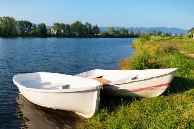 Два белых прогулочных катера на зеленом берегу на реке пришвартованы