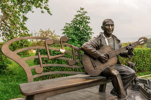 Бронзовый человек, играющий на гитаре, скамейка для влюбленных и молодоженов, уличный памятник, аттракционы, места для туристов, уличный музыкант