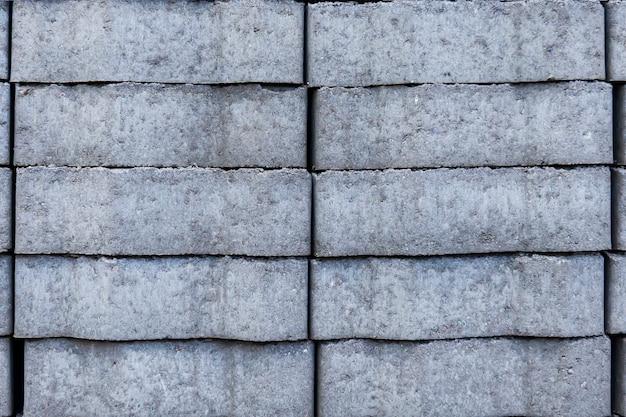 Серый текстурированный фон, бордюрный камень, заложенный в стопку