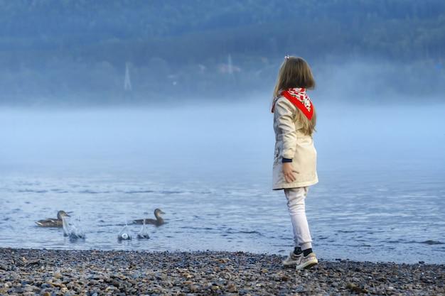 Девушка в бежевом пиджаке и красном шарфе кормит уток, бросая в воду еду и хлеб. вид со спины. река енисей, красноярск, россия, туманный вечер,