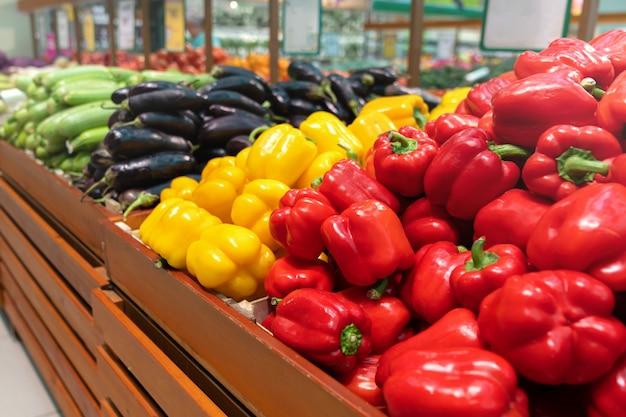 スーパーマーケットや食料品店のカウンターで整理されたピーマンの山。赤、オレンジ、黄色のピーマン