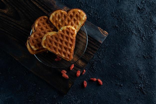 ベリーと暗い木製のハートの形のワッフル。デザート