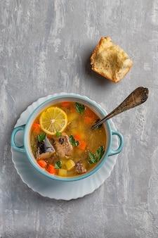 ジャガイモとニンジン、レモンとパンのスライスをコンクリートの背景にした魚のスープ