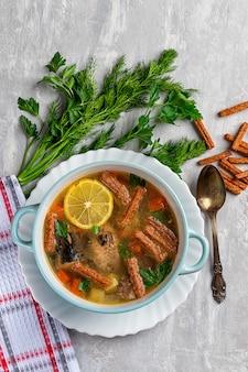 作りたてのレモンのスライスとコンクリートの背景に缶詰の魚のスープ