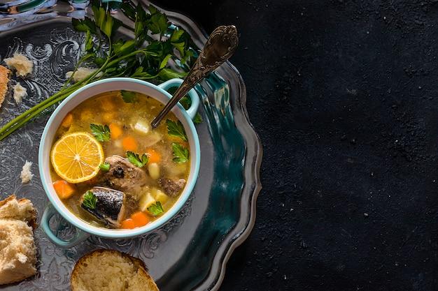 ジャガイモとニンジンのマグロのスープ、ハーブ入りの銀のトレイ