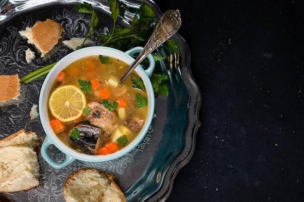 ポテトとニンジンの魚のスープ、レモンのスライスが入った銀のトレイ