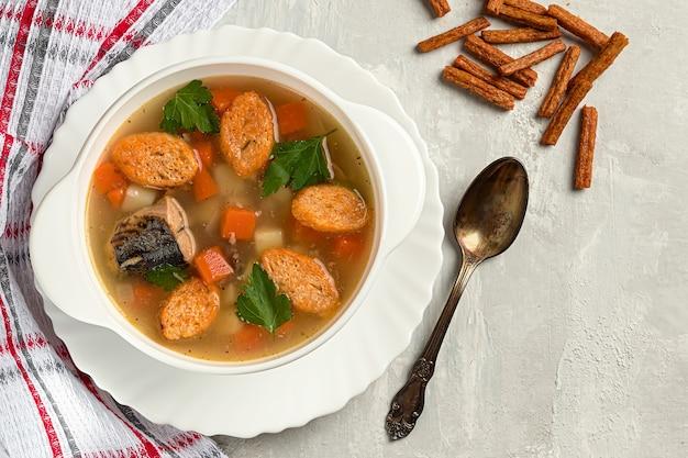 緑とクラッカーとコンクリートの背景に、ジャガイモとニンジンの魚のスープ