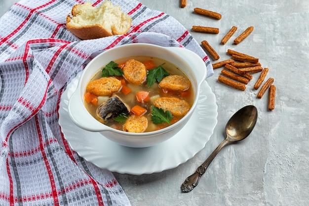 ハーブとコンクリートの背景にクラッカーと作りたてのツナの缶詰スープ