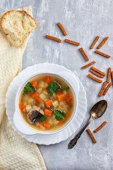 緑とクラッカーとコンクリートの背景に、ジャガイモとニンジンのマグロのスープ