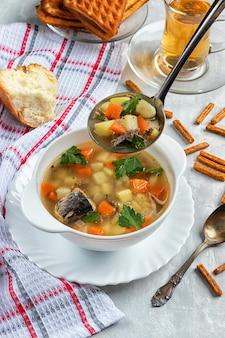 Свежеприготовленный консервированный суп из тунца с крекерами на бетонном фоне с половником
