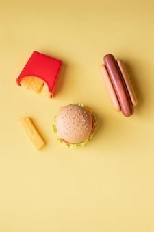 プラスチックのハンバーガー、サラダ、トマト、黄色の背景にホットドッグとジャガイモをフライパン