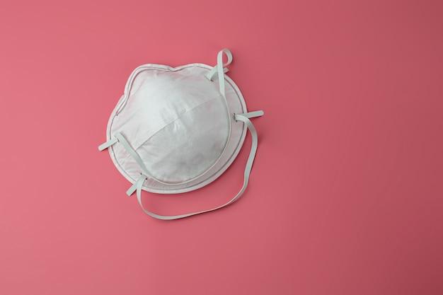 医療用マスクの分離。ウイルス、インフルエンザ、コロナウイルスに対する気道の保護。医療と外科のコンセプトです。ピンクの背景、危険