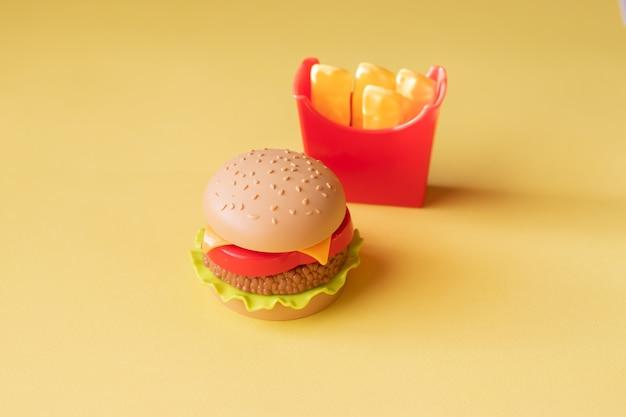 プラスチックのハンバーガー、サラダ、トマト、黄色の背景にジャガイモをフライパン