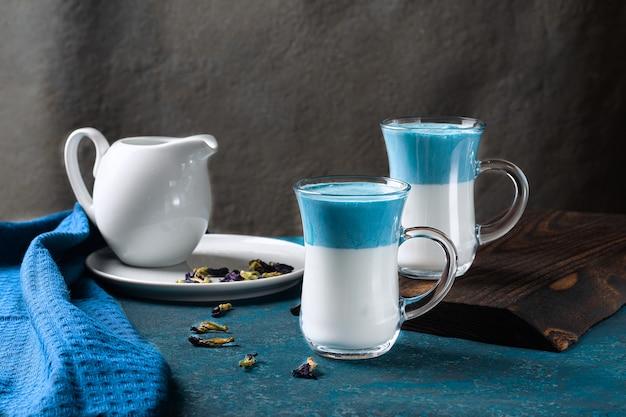 Латте матча далгона. горячее свежее молоко с голубыми цветами гороха бабочки