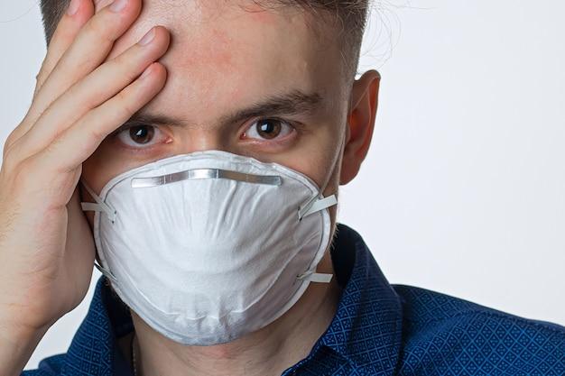 白いテーブルにコロナウイルスとさまざまな感染症検疫、病気に対する保護マスクを身に着けている若い男