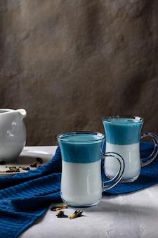 ラテ抹茶ダルゴナ。青い蝶エンドウ豆の花と新鮮な牛乳。ライトグレーのテーブルの上。垂直方向