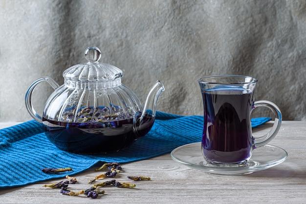減量のための熱い豆茶蝶(エンドウ豆の花、ブルーピース)のカップ、灰色の木製のテーブルのデトックス