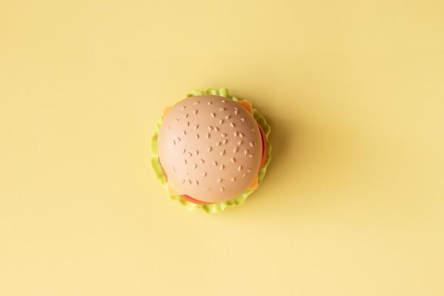 プラスチックのハンバーガー、サラダ、トマト、黄色の背景に