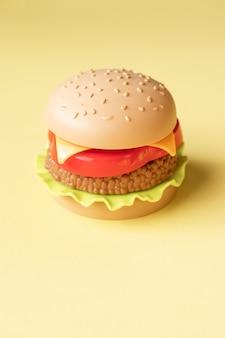 プラスチック製のハンバーガー、サラダ、トマト、黄色の背景