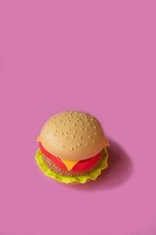 プラスチックのハンバーガー、サラダ、トマト、ピンクの背景