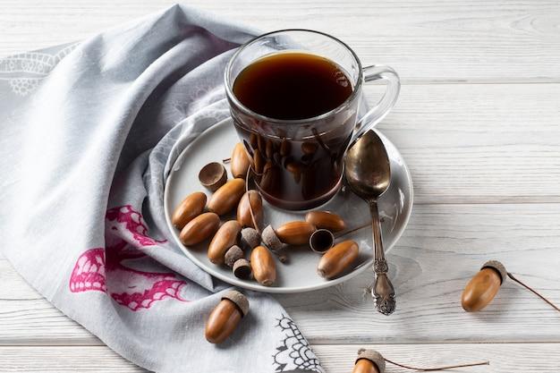 Горячий кофе из желудей в стакане - тонизирующий напиток с кофейным вкусом, насыщенным цветом и приятным ароматом.