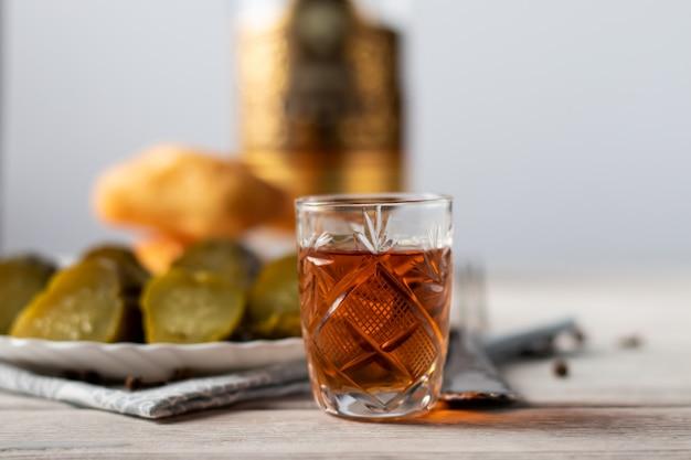 На деревянном столе стоит стакан коньяка, закуска из кусочка темного шоколада и бутылка алкоголя