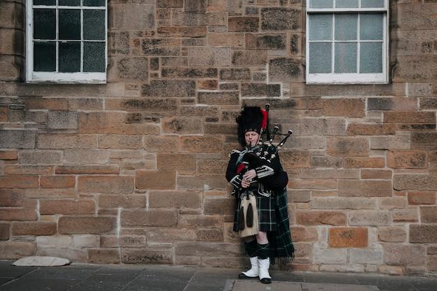 スコットランドの男が通りでバグパイプを演奏