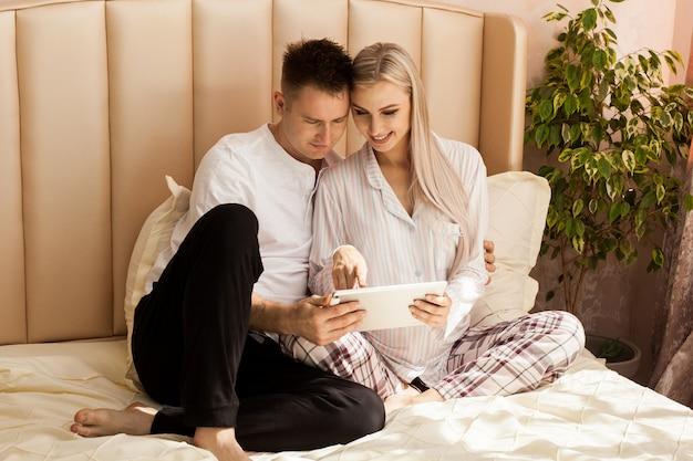 妊娠中の女性と男性がタブレットを使用して自宅のベッドに横たわっています。