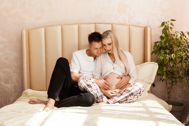 妊娠と人々のコンセプト-自宅で妊娠中の女性を抱いて幸せな男